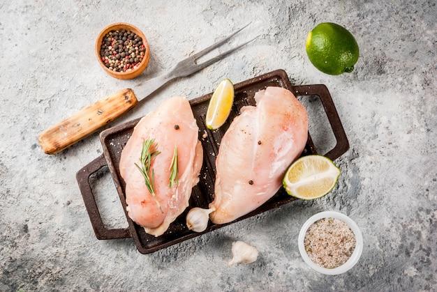 Rauw vlees, klaar voor grill of barbecue kipfilet filet, met olijfolie, kruiden en specerijen op grijze stenen achtergrond, kopie ruimte bovenaanzicht
