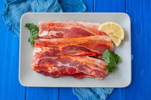 Rauw vlees met kruiden en knoflook voor grill op schotel