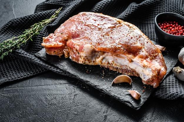 Rauw vlees met kruiden en specerijen. gemarineerde varkenssteak. ingrediënten om te koken