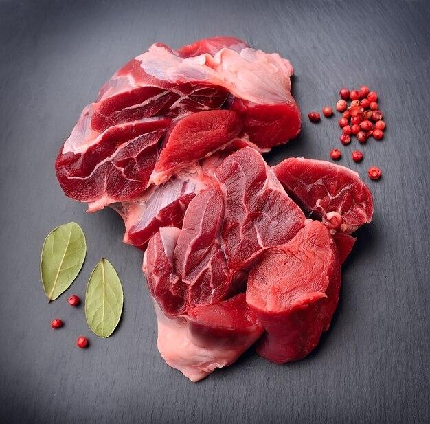Rauw vlees met kruiden op zwarte achtergrond.