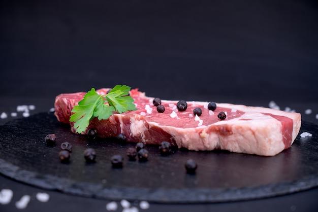 Rauw vlees op een bord met zout en jeneverbessen
