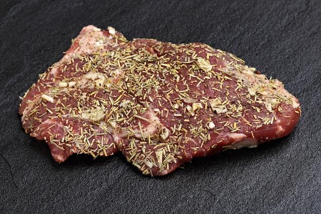 Rauw vlees op een donkere achtergrond met kruiden bereid om te grillen.