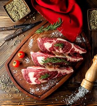 Rauw vlees plakjes gegarneerd met kruiden en zout