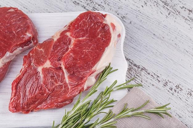 Rauw vlees. rauwe biefstuk op een witte snijplank met rozemarijn.