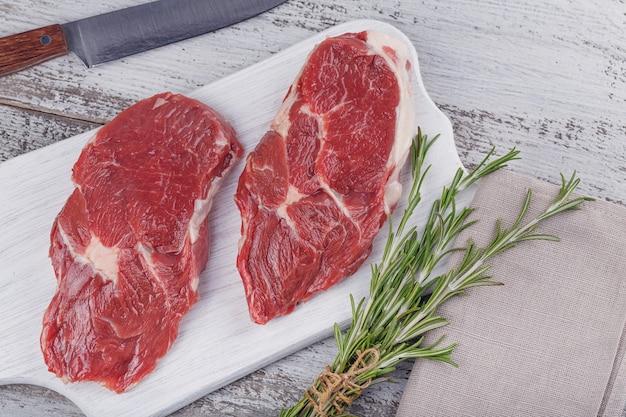 Rauw vlees. rauwe verse biefstuk op een witte snijplank met rozemarijn. bovenaanzicht