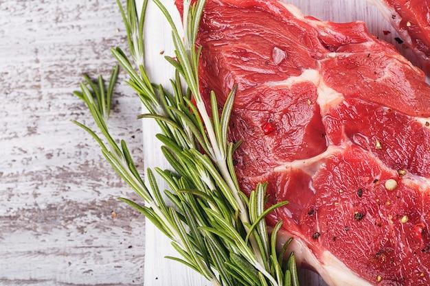 Rauw vlees. rauwe verse biefstuk op een witte snijplank met rozemarijn en kruiden. detailopname