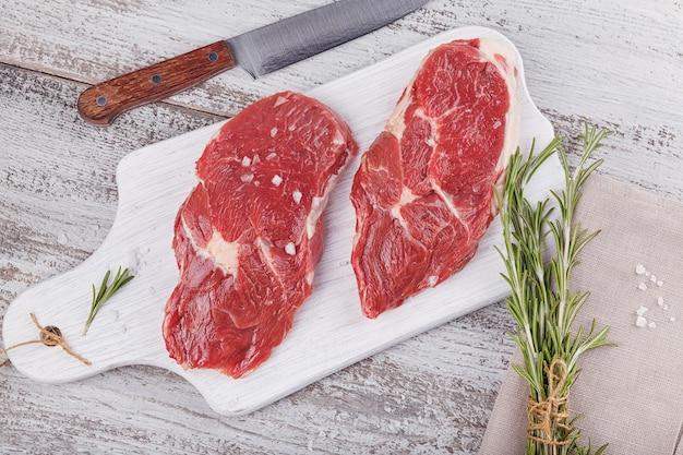 Rauw vlees. rauwe verse biefstuk op een witte snijplank met rozemarijn en kruiden. plat leggen