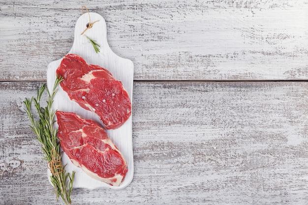 Rauw vlees. rauwe verse biefstuk op een witte snijplank met rozemarijn en kruiden.