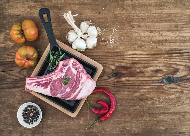 Rauw vlees ribeye steak met peper, zout, chili, knoflook, spinazie, heirloom tomaten en rozemarijn in kookpan op rustieke houten tafel