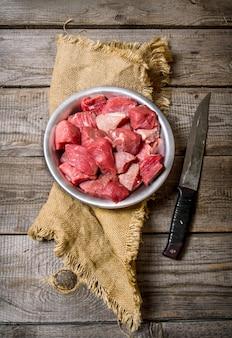 Rauw vlees snijden een groot mes op een houten tafel