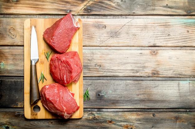 Rauw vlees. stukjes rundvlees met een mes. op een houten.