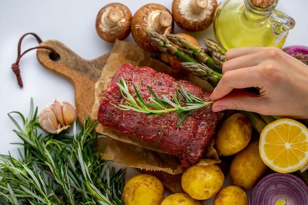 Rauw vlees van rood rundvlees met groene rozemarijn en verse groenten op een houten snijplank
