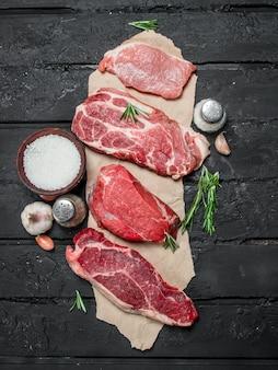 Rauw vlees. varkens- en biefstuk met kruiden en specerijen. op een zwarte rustiek.