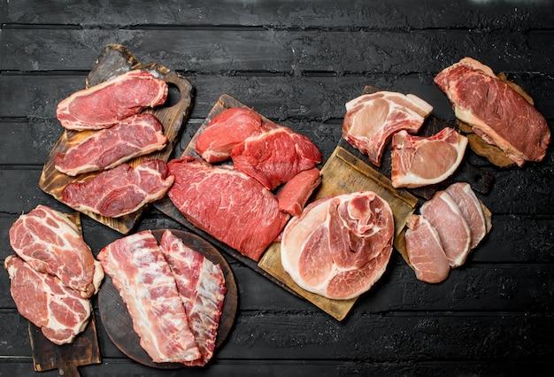 Rauw vlees. verschillende soorten varkensvlees en rundvlees. op een zwarte rustieke ondergrond.