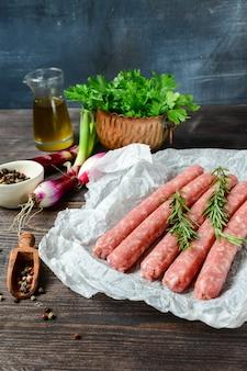 Rauw vlees worsten voor barbecue of hotdog. paarse uien, zout en peper, verse oregano voor marinade. grill familiediner