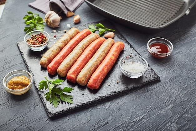 Rauw vlees worstjes op een leisteen bord, met kruiden en specerijen en een vierkante grillpan. uitzicht van boven.