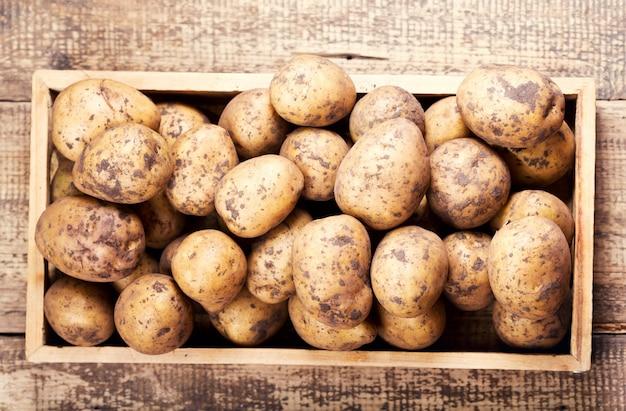 Rauwe aardappelen in de houten kist, bovenaanzicht