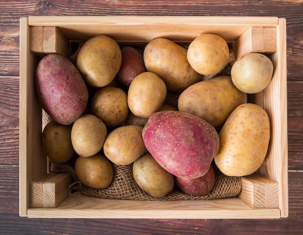 Rauwe aardappelen in houten kist
