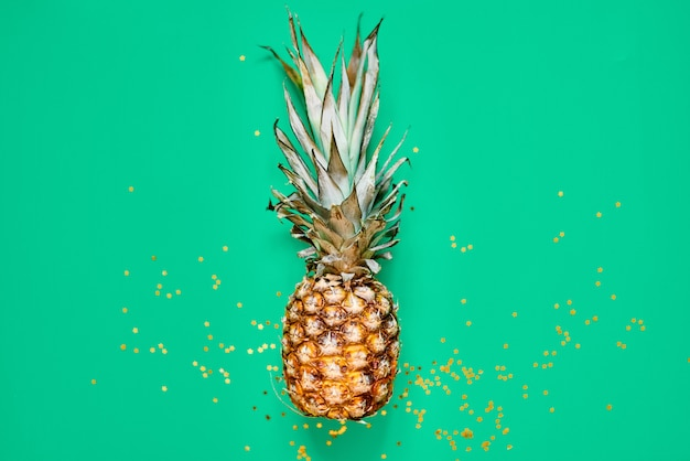 Rauwe ananas met gouden glitter. plat lag tropisch concept