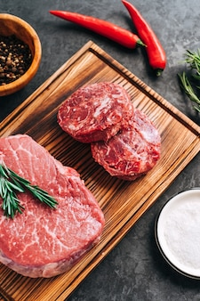 Rauwe biefstuk en gehakte ronde biefstuk voor hamburgers op een houten bord met rozemarijn chili peper