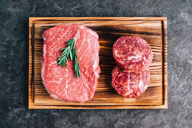 Rauwe biefstuk en gehakte ronde biefstuk voor hamburgers op een houten bord