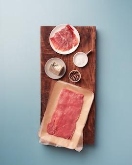Rauwe biefstuk en ingrediënten voor het vullen van ham blauwe kaas zout en peper om te kruiden
