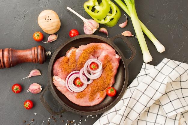 Rauwe biefstuk, entrecote met kruiden voor het koken van vlees in een gietijzeren pan met uien, knoflook en tomaat. zwarte achtergrond. bovenaanzicht.