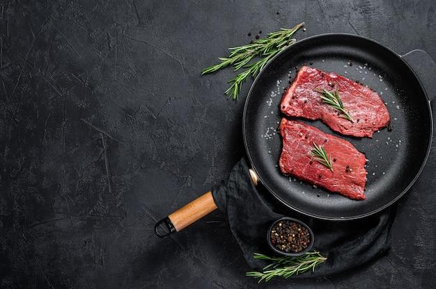 Rauwe biefstuk in een koekenpan. rund vlees. zwarte achtergrond. bovenaanzicht. ruimte voor tekst