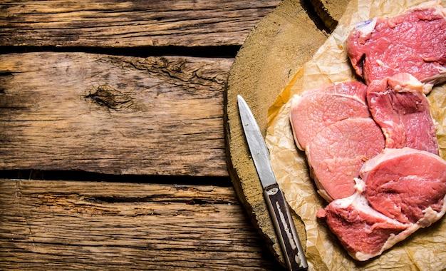 Rauwe biefstuk met een mes op een houten standaard op een houten tafel