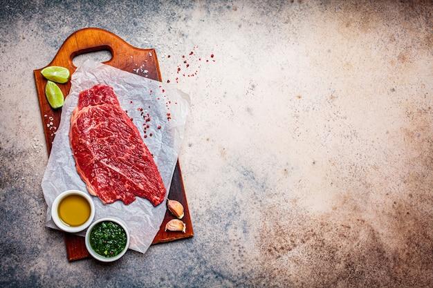 Rauwe biefstuk met kruiden en chimichurri saus op houten bord, donkere achtergrond, kopie ruimte.