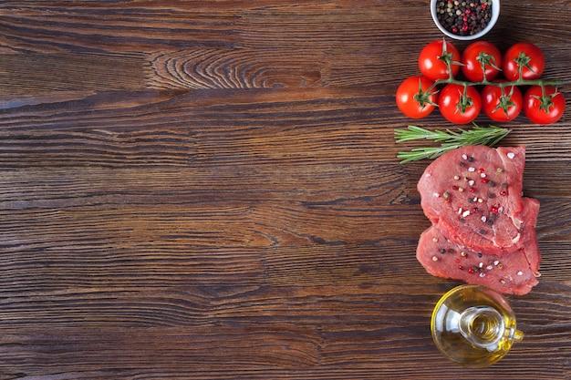 Rauwe biefstuk met kruiden en ingrediënten voor het koken op bruin houten oppervlak.