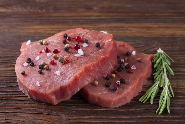 Rauwe biefstuk met rozemarijn en kruiden op bruine houten achtergrond