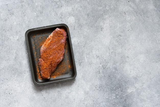 Rauwe biefstuk op een zwarte trayken betonnen achtergrond. uitzicht van boven.