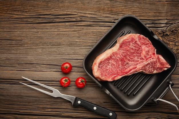 Rauwe biefstuk op het bot in een grillpan.