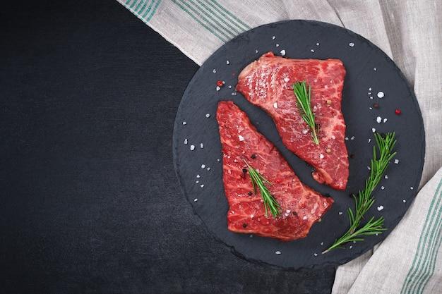 Rauwe biefstuk op snijplank met rozemarijn en kruiden