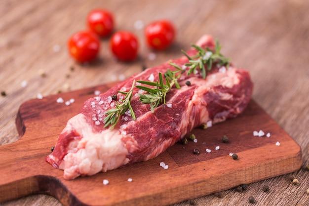 Rauwe biefstuk van de biefstuk met kruiden en specerijen op houten tafel