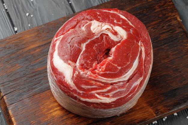 Rauwe biefstuk van de ossenhaas op zwarte houten tafel
