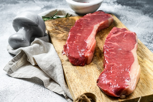 Rauwe biefstuk, vers vlees, gemarmerd rundvlees. donkere achtergrond. plat liggen