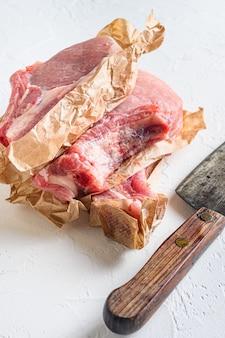 Rauwe biologische bio pork belly grill. zijaanzicht verticaal. met vlees slager hakmes