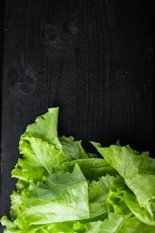 Rauwe biologische groene, eiken sla, op zwarte houten tafel met kopieerruimte voor tekst