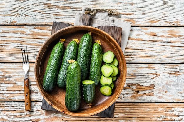 Rauwe biologische komkommers in een houten bord. witte houten achtergrond. bovenaanzicht.