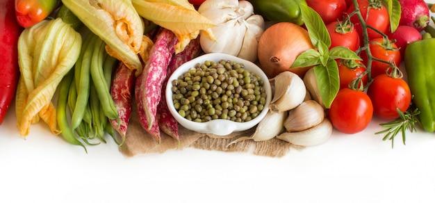 Rauwe biologische mungbonen in een kom en rauwe groenten