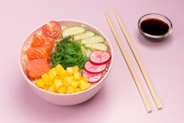 Rauwe biologische rode vis poke bowl met rijst en groenten