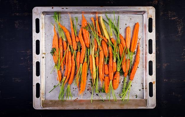 Rauwe biologische wortelen met tijm, honing en citroen bereid op een bakplaat