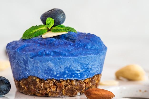 Rauwe bosbessen, acai en vlindererwtenbloem veganistische cake met verse bessen, munt, noten. gezond veganistisch voedselconcept