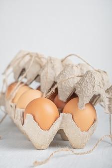 Rauwe bruine dozijn kippeneieren in half gesloten kringlooppapier container witte houten tafel