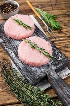 Rauwe burgerpasteitje van biologisch kip- en kalkoenvlees met tijm en rozemarijn. houten achtergrond. bovenaanzicht.