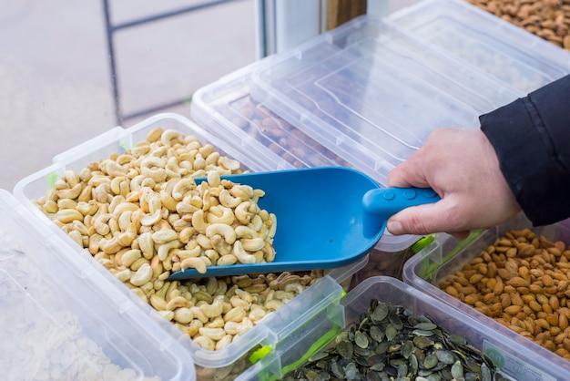 Rauwe cashewnoten close-up in houten kom op rouwgewaad close-up verkoper met behulp van een spatel plukt cashewnoten uit een container. achter de toonbank
