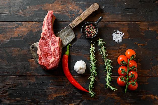 Rauwe delmonico-lapje vlees op vleesmes. biologische boerderij gemarmerd prime black angus beef. donkere houten achtergrond. bovenaanzicht. met kruiden, peperkorrels, chili, rozemarijn, zout, knoflook. niemand