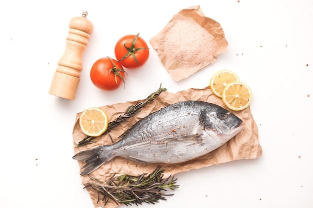 Rauwe dorada-vis of goudbrasem op ijs met citroen, tomaat, rozemarijn en zout over wit oppervlak, plat gelegd, bovenaanzicht